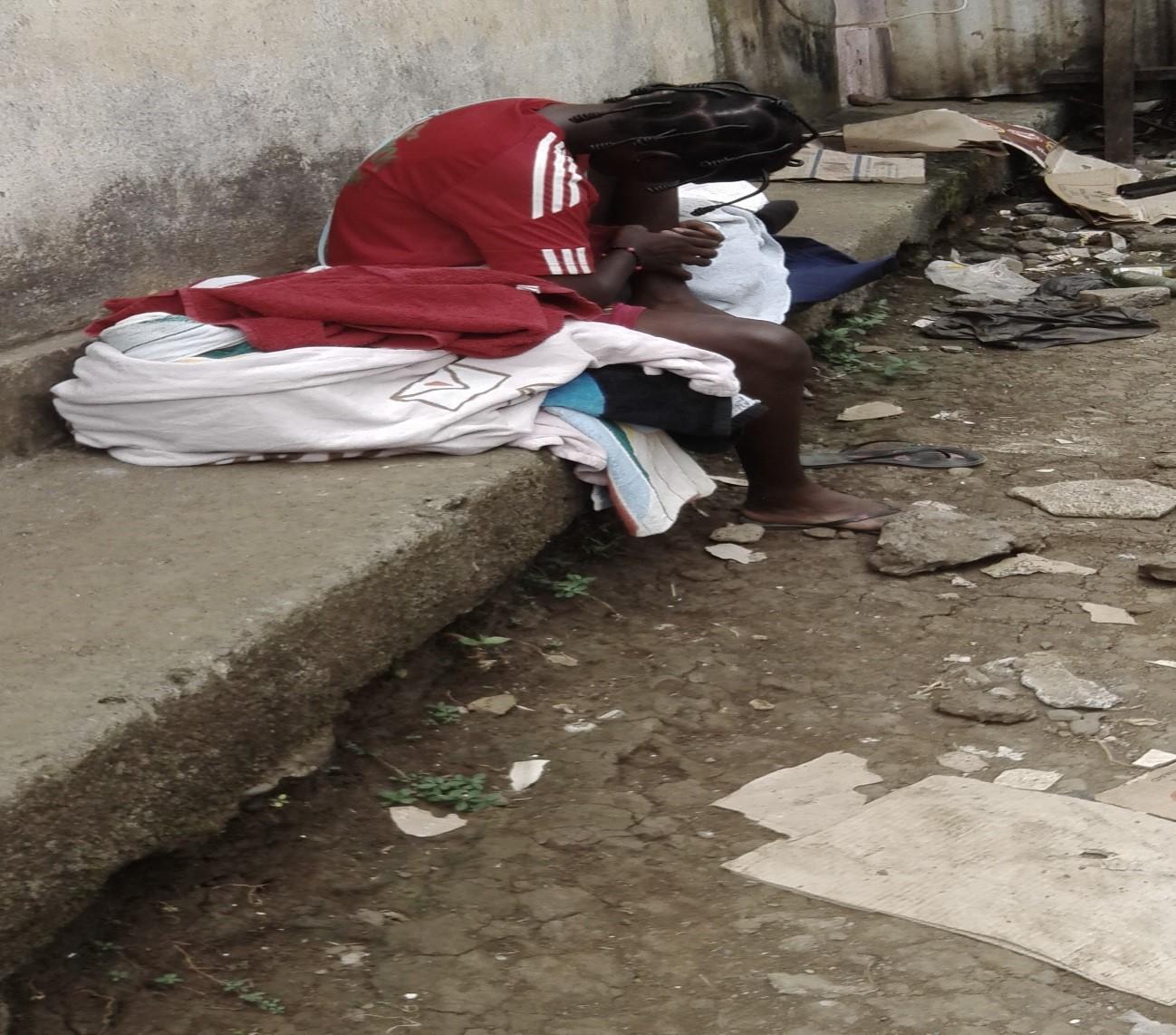 Foto, Niña descansando entre las ropas usadas que vende en los barrios