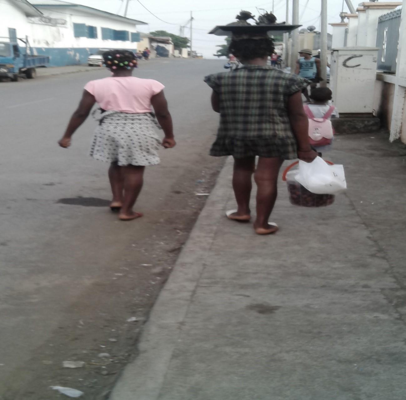 Foto, Niña recorriendo las aceras de la ciudad vendiendo envueltos de cacahuete y caracol