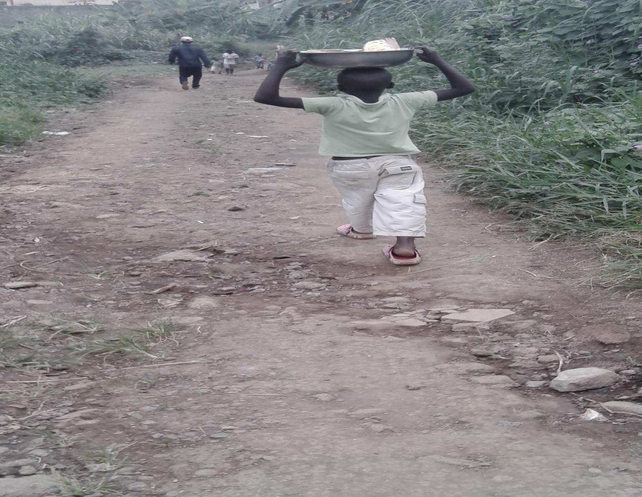 Foto, Niño vendiendo pedazos de yaca bajo el sol
